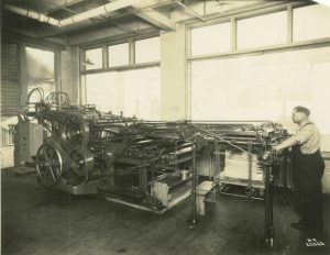 Worker operates a specialized printing press at the Krueger Printing Company.