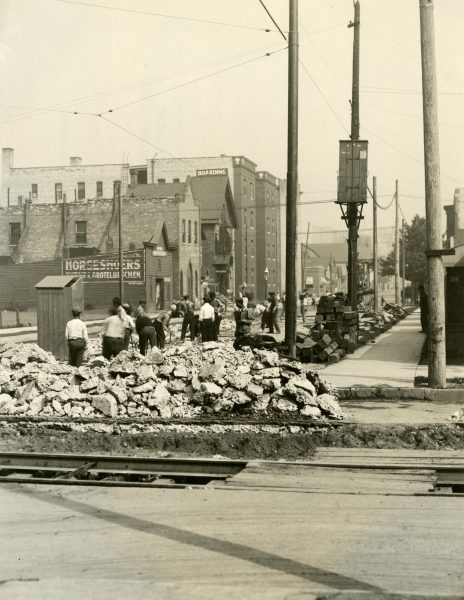 Men working on building the road at North 7th Street and West Wells in this 1913 photograph.