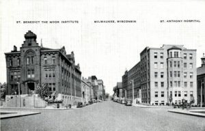 This photograph, looking north on 10th Street just south of State Street, captures three elements of the St. Benedict the Moor Mission in the 1930s: on the far right a sliver of the church (with cupola along roofpeak), St. Anthony Hospital (right of center), and the boarding school (on the left, for decades the original home of Marquette College).