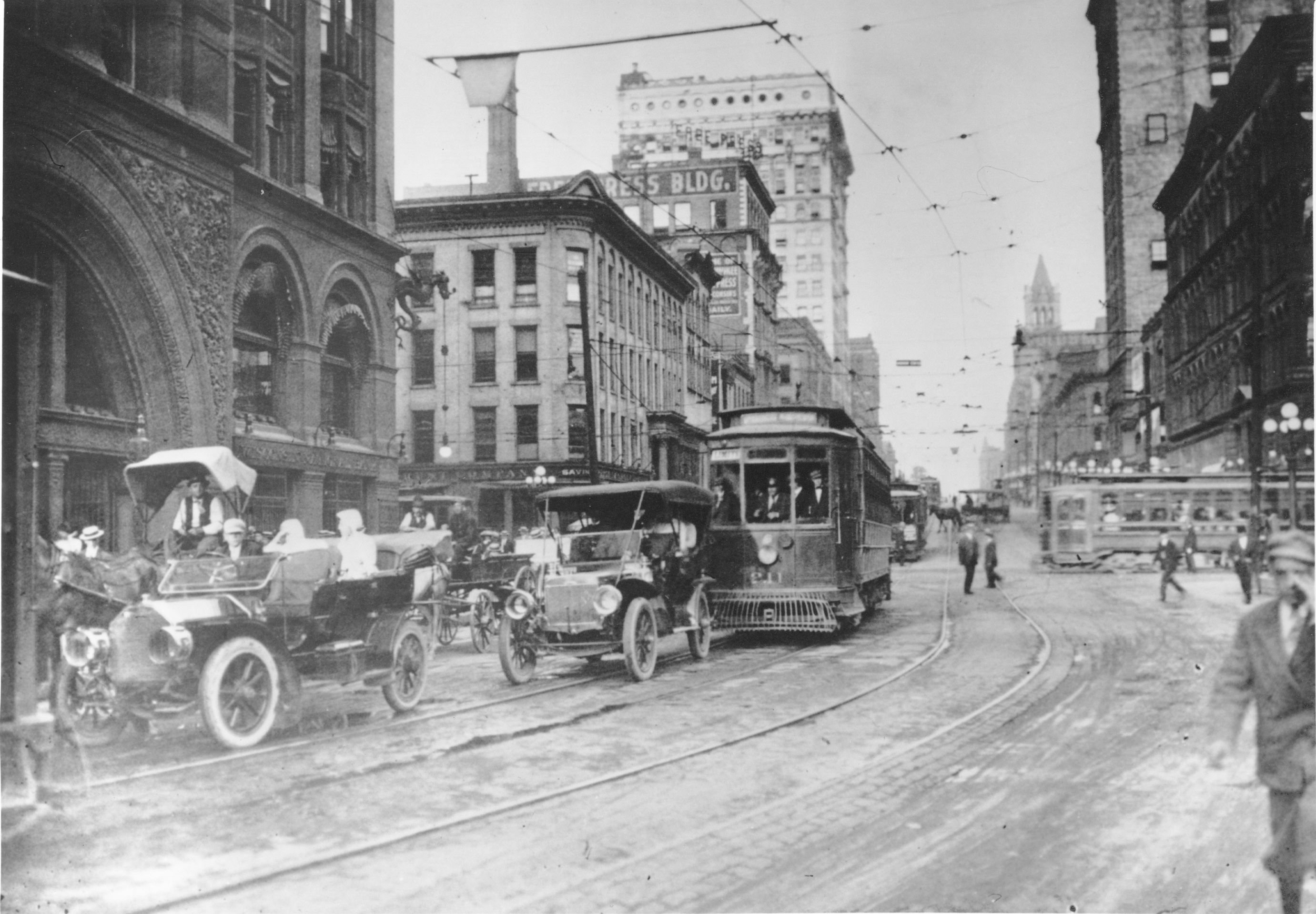 Automobiles, a horse and buggy, and trolleys share the road on E. Wisconsin Avenue in the early twentieth century.