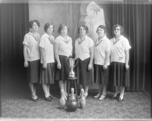 Group photograph of a women's bowling team standing behind a trophy in 1928.