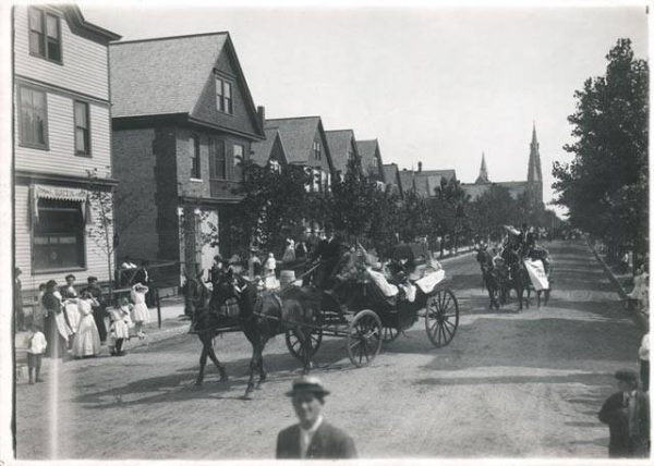 Carriages parade past Frank Burczyk Saloon on North Bremen Street in Riverwest.
