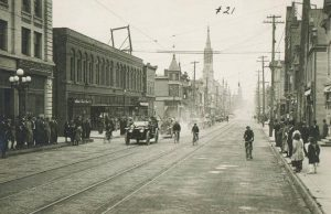 This 1914 photograph shows West Mitchell Street's use by cars and bicycles, as well as streetcars and pedestrians.