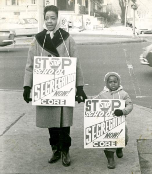 A woman and small child carry signs calling for the end of Milwaukee school segregation in 1964.