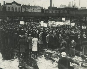 A large group of demonstrators gathered in Haymarket Square on February 13, 1930 to listen to Communist speakers, protest working conditions, and call for the recognition of the Soviet Union.