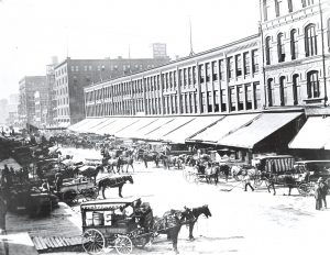 Horse-drawn carts full of produce line Commission Row on Broadway Street.