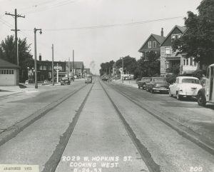 This westward view of the 2000 block of Hopkins Street shows automobiles, houses, two gas stations, and trolley tracks in 1953.