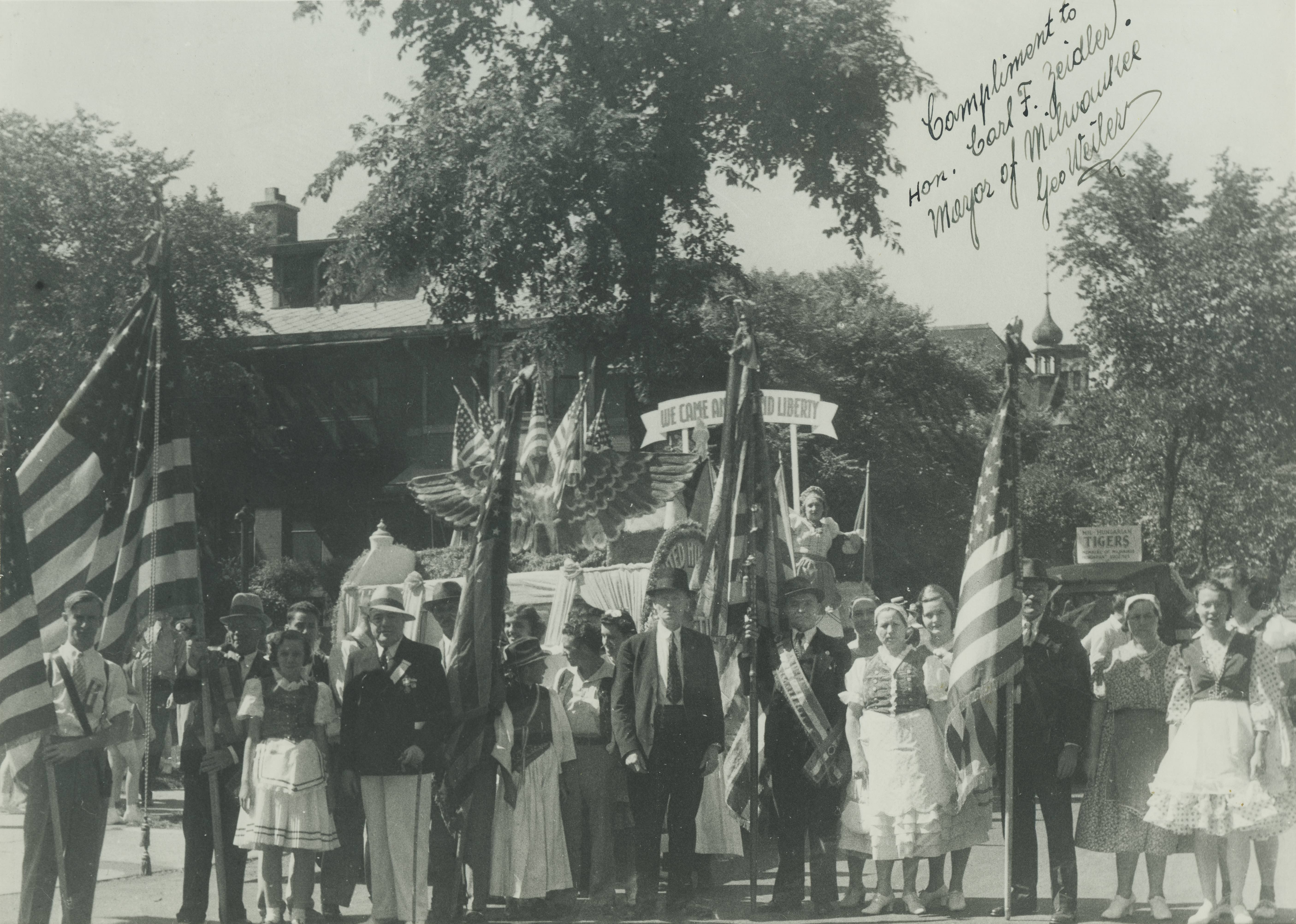 <table class=&quot;lightbox&quot;><tr><td colspan=2 class=&quot;lightbox-title&quot;>Hungarians' Liberty Float</td></tr><tr><td colspan=2 class=&quot;lightbox-caption&quot;>A group of of people from the U.S. American Hungarian Societies of Wisconsin stand in front of their float at the 1940 Midsummer Festival.</td></tr><tr><td colspan=2 class=&quot;lightbox-spacer&quot;></td></tr><tr class=&quot;lightbox-detail&quot;><td class=&quot;cell-title&quot;>Source: </td><td class=&quot;cell-value&quot;>From the Historic Photo Collection of the Milwaukee Public Library. Reprinted with permission.<br /><a href=&quot;http://content.mpl.org/cdm/singleitem/collection/HstoricPho/id/5912/rec/1&quot; target=&quot;_blank&quot;>Milwaukee Public Library</a></td></tr><tr class=&quot;filler-row&quot;><td colspan=2>&nbsp;</td></tr></table>