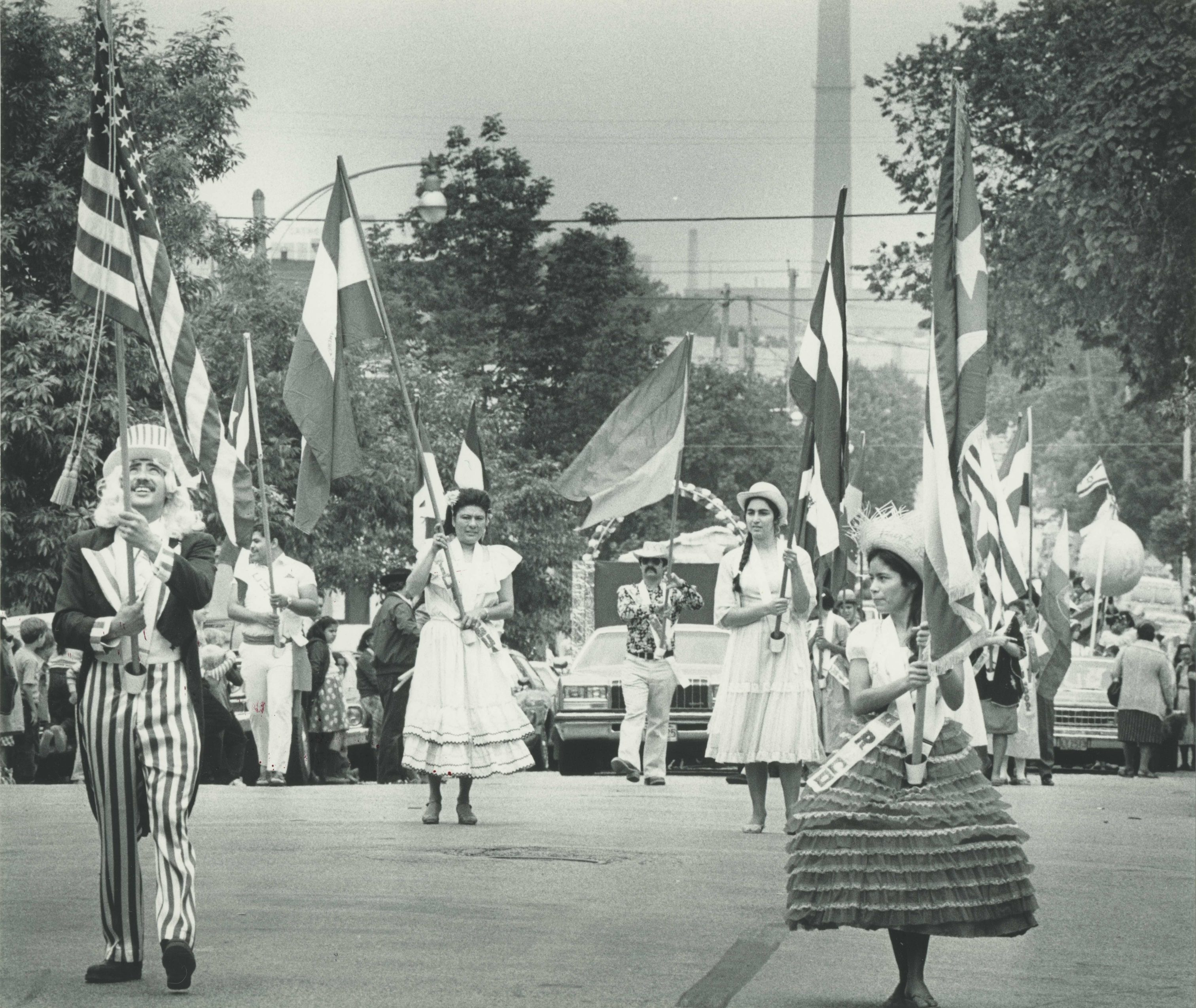 Men and women wearing costumes and carrying flags parade down the street at part of Mexican Fiesta in 1984.