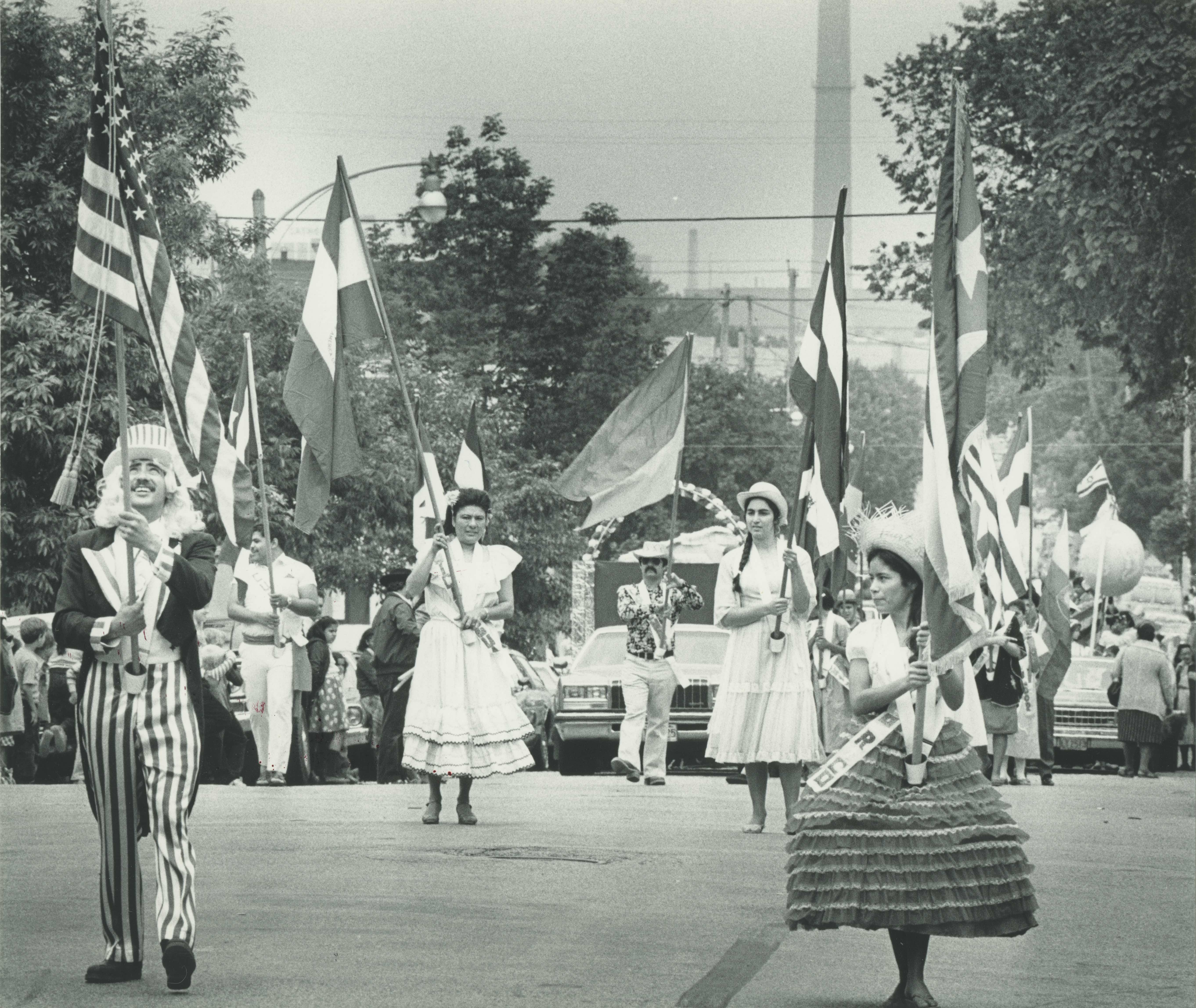 <table class=&quot;lightbox&quot;><tr><td colspan=2 class=&quot;lightbox-title&quot;>Mexican Fiesta Parade</td></tr><tr><td colspan=2 class=&quot;lightbox-caption&quot;>Men and women wearing costumes and carrying flags parade down the street at part of Mexican Fiesta in 1984.</td></tr><tr><td colspan=2 class=&quot;lightbox-spacer&quot;></td></tr><tr class=&quot;lightbox-detail&quot;><td class=&quot;cell-title&quot;>Source: </td><td class=&quot;cell-value&quot;>From the Historic Photo Collection of the Milwaukee Public Library. Reprinted with permission.<br /><a href=&quot;http://content.mpl.org/cdm/singleitem/collection/HstoricPho/id/5665/rec/3&quot; target=&quot;_blank&quot;>Milwaukee Public Library</a></td></tr><tr class=&quot;filler-row&quot;><td colspan=2>&nbsp;</td></tr></table>
