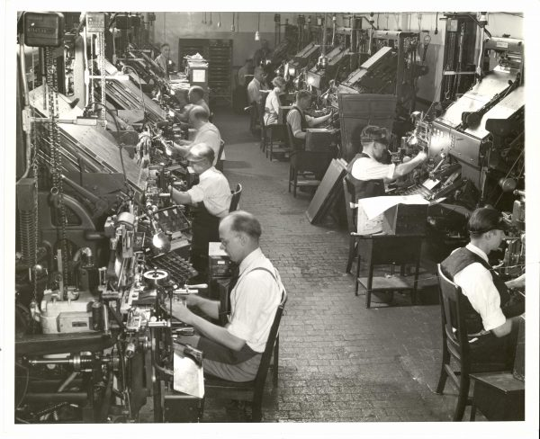 Two rows of employees work at Intertype machines. Most of the employees are men, but there is one woman on the right, near the back.