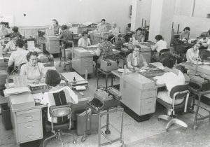 A room full of women work at desks at the Milwaukee Journal. Each woman is wearing a headset, suggesting that this is the steno pool.