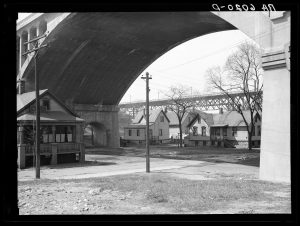 Before the Wisconsin Avenue viaduct was torn down, many homes were constructed underneath it, as featured in this photograph from 1936.