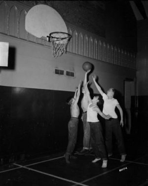A group of four boys play basketball indoors in 1948.