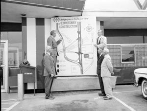 Men examine a proposed plan for Milwaukee-area expressways in this stage photograph from June 1959.