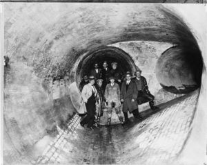 This photograph of men standing inside a sewer tunnel under construction provides a sense of scale and of the materials used in building them.