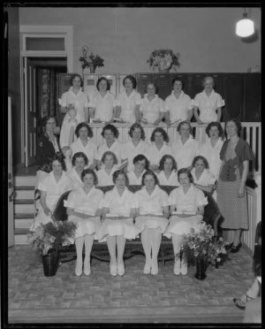 A group of graduates of the Wisconsin Academy of Cosmetic Art, adjacent to the Kletz Beauty Shop in Milwaukee, pose with their certificates in 1932.