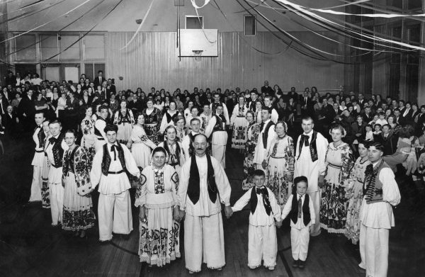 A group of Croatians in Milwaukee are gathered together in this photograph from December, 1933. Many people wear traditional clothing.