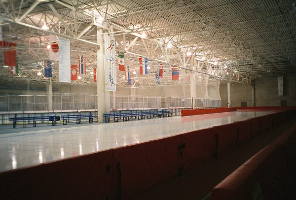 Interior photograph of the Pettit National Ice Center with international flags hanging from the rafters.