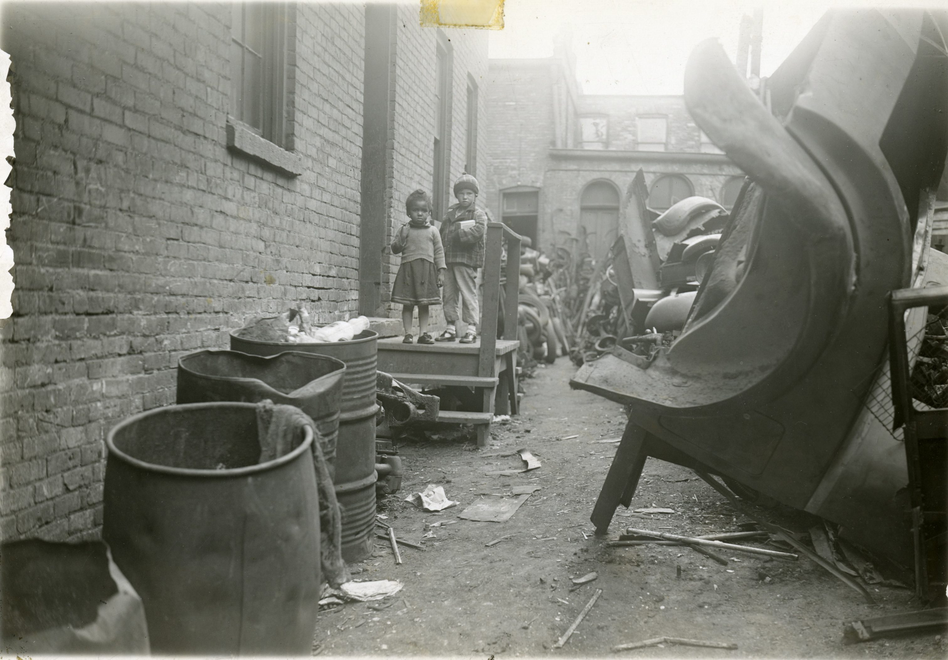 Two small children stand on the rear porch of an apartment building once located on N. 8th Street. The yard is filled with scrap metal from junked cars.