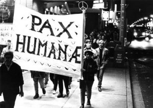 "Marquette University students march down a sidewalk carrying a banner that reads ""Pax Humanae"" in 1970."