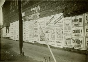 Campaign posters cover this brick wall on Wells Street in 1932. Candidates include Benson for Sheriff, Joseph Shinners for Sheriff, Raymond Cannon for Congress, and Zabel for District Attorney.