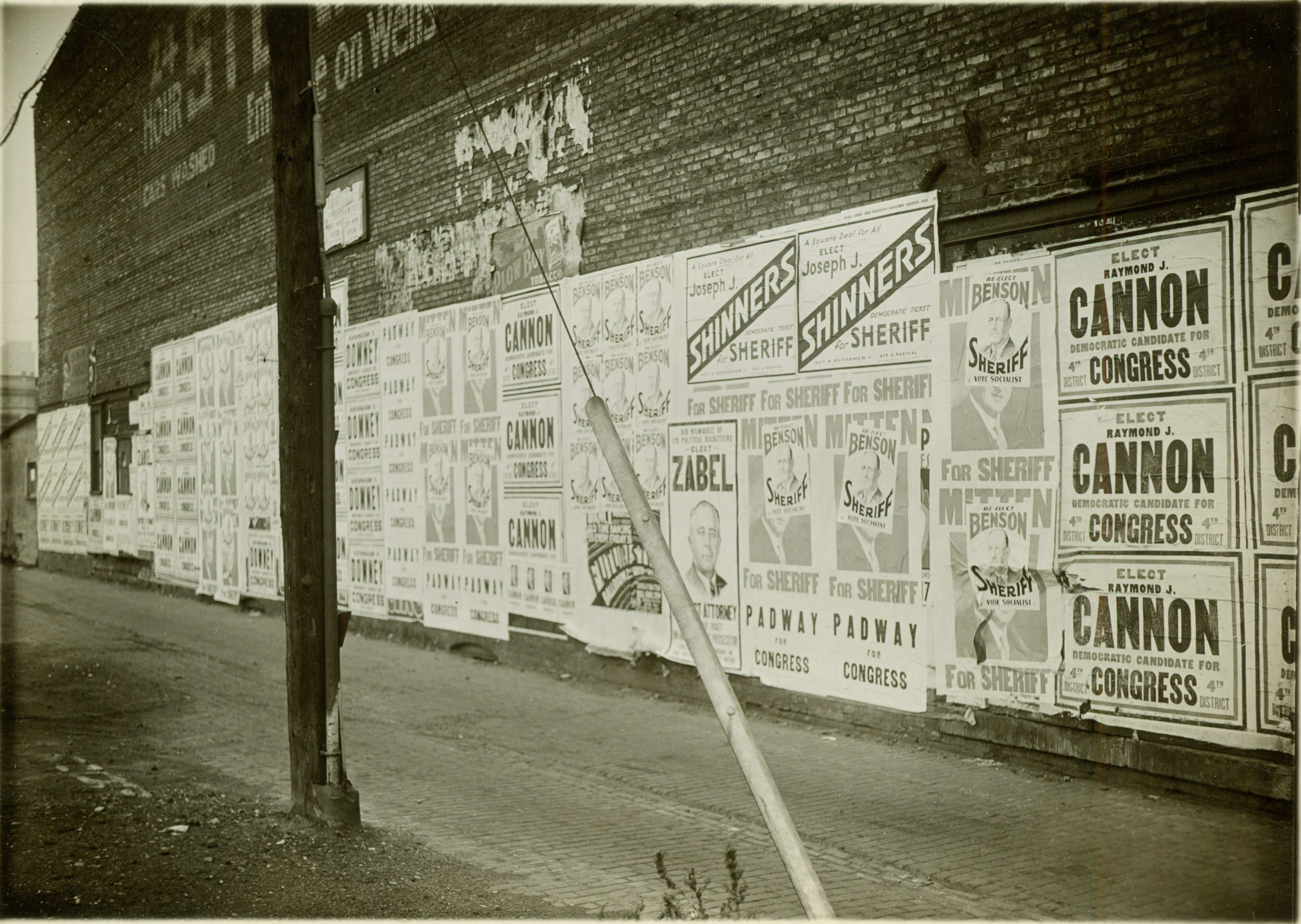 <table class=&quot;lightbox&quot;><tr><td colspan=2 class=&quot;lightbox-title&quot;>Political Posters in Milwaukee</td></tr><tr><td colspan=2 class=&quot;lightbox-caption&quot;>Campaign posters cover this brick wall on Wells Street in 1932. Candidates include Benson for Sheriff, Joseph Shinners for Sheriff, Raymond Cannon for Congress, and Zabel for District Attorney.</td></tr><tr><td colspan=2 class=&quot;lightbox-spacer&quot;></td></tr><tr class=&quot;lightbox-detail&quot;><td class=&quot;cell-title&quot;>Source: </td><td class=&quot;cell-value&quot;>From the Historic Photo Collection of the Milwaukee Public Library. Reprinted with permission. <br /><a href=&quot;http://content.mpl.org/cdm/singleitem/collection/HstoricPho/id/8987/rec/5&quot; target=&quot;_blank&quot;>Milwaukee Public Library</a></td></tr><tr class=&quot;filler-row&quot;><td colspan=2>&nbsp;</td></tr></table>