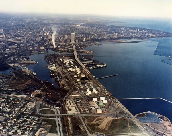 In this 1975 aerial photograph, the docks of the outer harbor at Port Milwaukee can be seen on the east (or right-hand) side of Jones Island and the inner harbor on the west (or left-hand) side of the island.  The smoke, left of center, is arising from the sewerage treatment plant, with I-794 cutting lengthwise south to north along the island leading to the Hoan Bridge.
