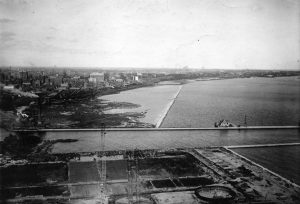 The metropolitan sewerage treatment plant is under construction at the northern tip of Jones Island in this photograph.  North of the inlet leading to the inner harbor is swampy land that eventually be filled in and transformed over time into the Summerfest Grounds.