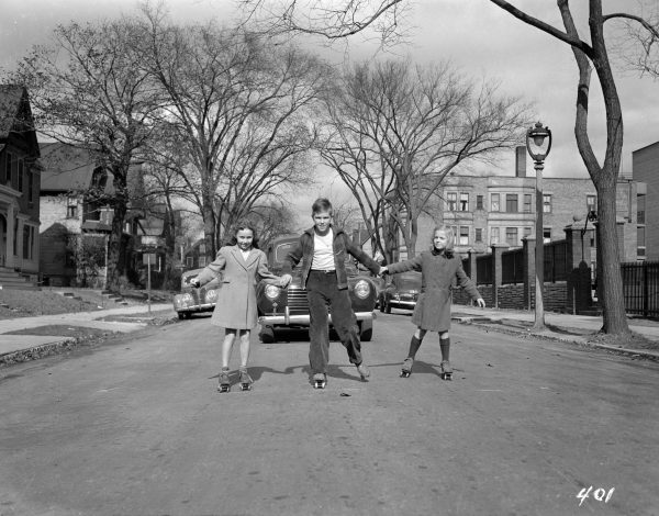 Three children roller skate down a Milwaukee street in this photograph from October 1943.
