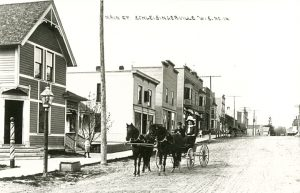 A view down Main Street in Slinger in 1910. The building foremost to the left was Schafer's Barber Shop, while the next building was the State Bank of Schleisingerville.