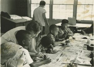 A woman works with a small group of children as part of the Milwaukee Handicraft Project, a public works project developed under the WPA during the Great Depression.