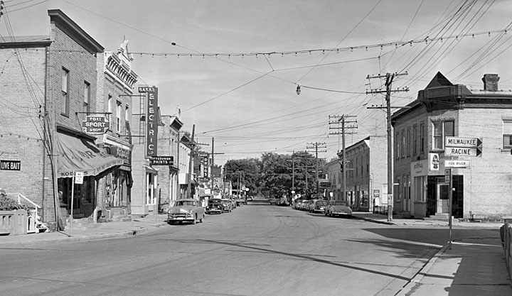 <table class=&quot;lightbox&quot;><tr><td colspan=2 class=&quot;lightbox-title&quot;>Main Street in Waterford</td></tr><tr><td colspan=2 class=&quot;lightbox-caption&quot;>Looking east down Main Street in the Racine County town of Waterford. Signs toward the cities of Milwaukee and Racine are visible on the right side of the photo.</td></tr><tr><td colspan=2 class=&quot;lightbox-spacer&quot;></td></tr><tr class=&quot;lightbox-detail&quot;><td class=&quot;cell-title&quot;>Source: </td><td class=&quot;cell-value&quot;>From the State of Wisconsin Collection of the UW Digital Collections Library. Image ID WI.wpl00722.bib. Photograph courtesy of Waterford Public Library's Local History Digital Collection. Fair use for nonprofit educational purposes.<br /><a href=&quot;http://digital.library.wisc.edu/1711.dl/WI&quot; target=&quot;_blank&quot;>UW Digital Collections Library</a></td></tr><tr class=&quot;filler-row&quot;><td colspan=2>&nbsp;</td></tr></table>