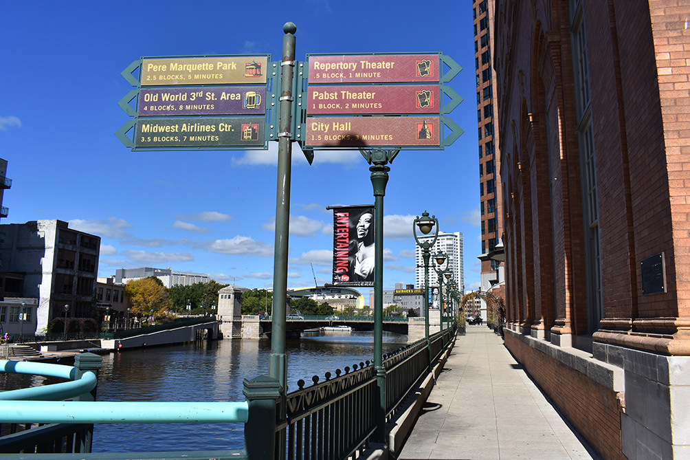 A modern view of Milwaukee's RiverWalk with signs directing pedestrians to area attractions.
