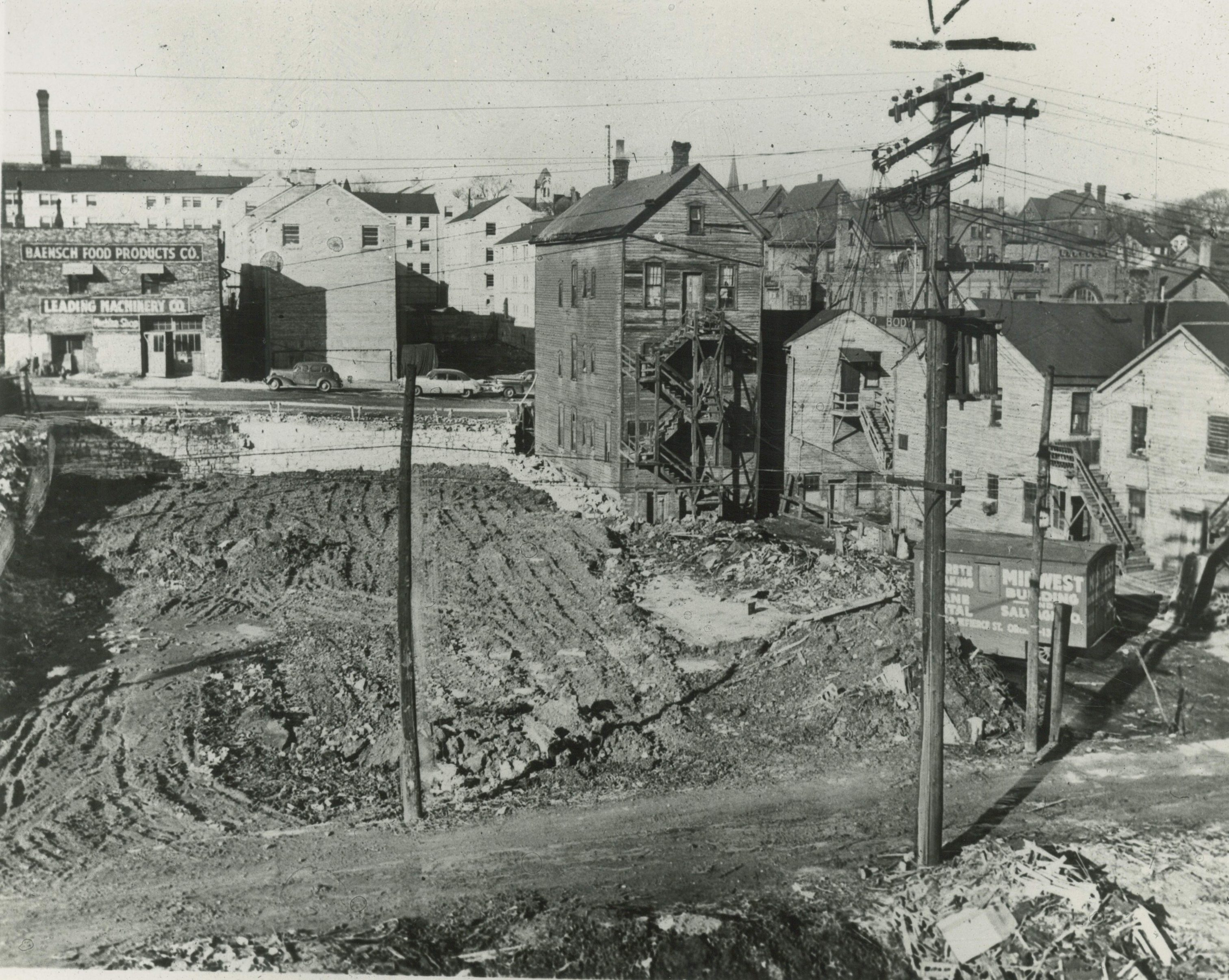 Photograph of an demolished lot and other housing structures on W. Fond Du Lac Avenue that were eventually torn down and replaced by the Hillside Housing Development.