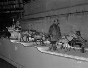 This float from Schuster's Christmas parade in 1943 features Santa Claus, his reindeer, and the character Me-Tik.