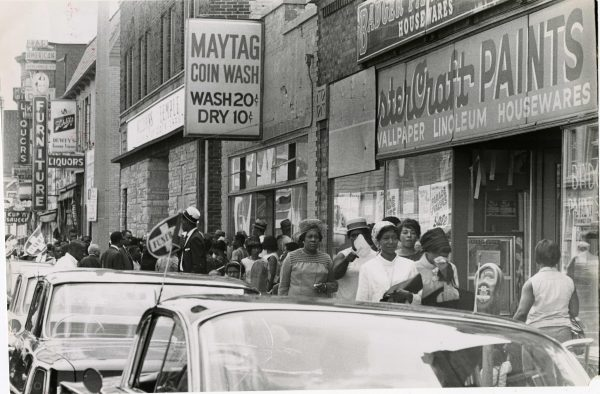 A crowd of people walk past the Badger Paint store on Teutonia Avenue where Clifford McKissick was shot and killed during the civil disorder of 1967.