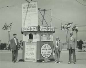 Three men stand beside a booth selling festival buttons for one dollar in 1941. The purchase of a button gave fairgoers admission to some of the festival's paid attractions and a chance to win a car.