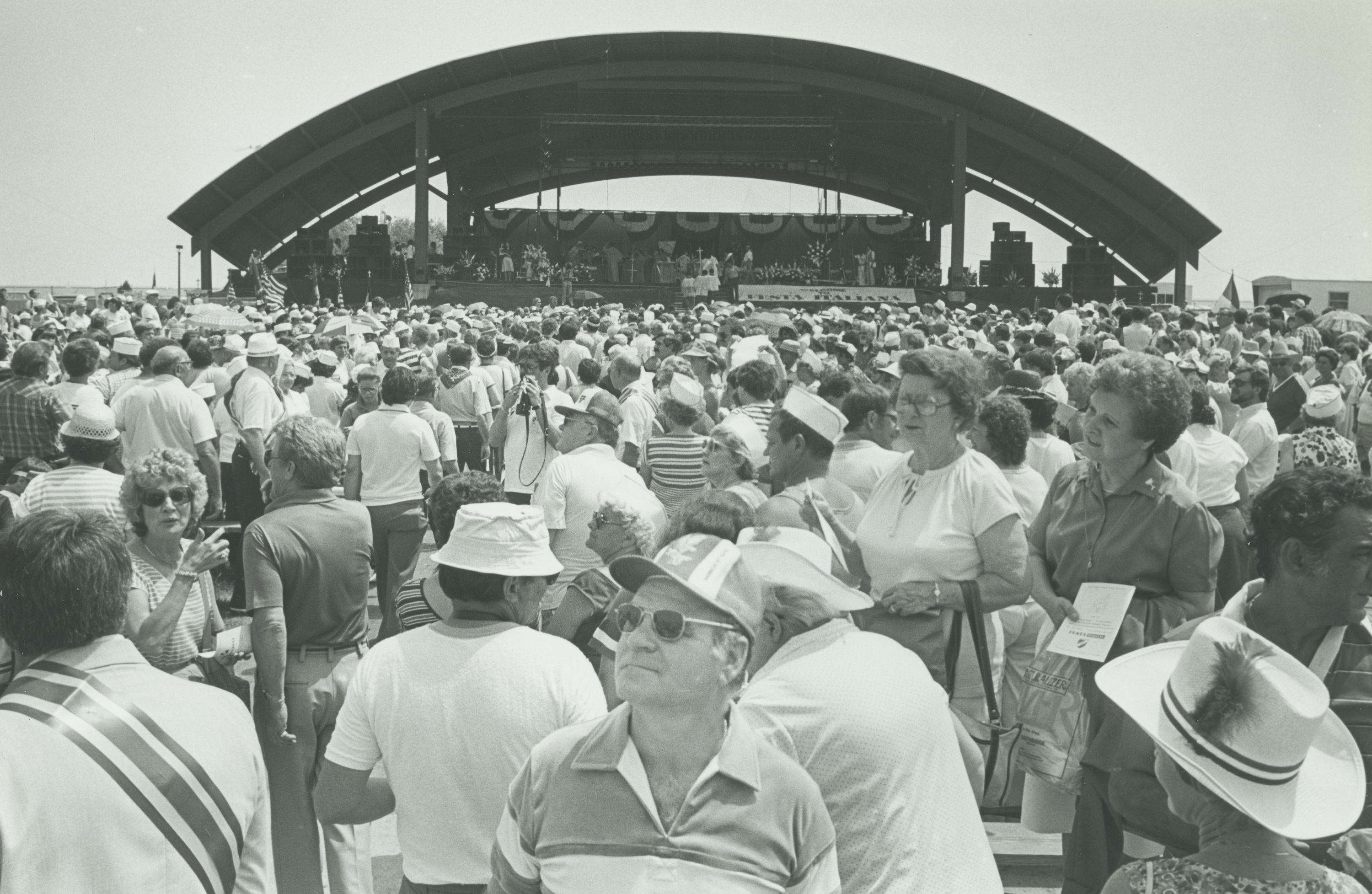 <table class=&quot;lightbox&quot;><tr><td colspan=2 class=&quot;lightbox-title&quot;>Mass at Festa Italiana</td></tr><tr><td colspan=2 class=&quot;lightbox-caption&quot;>A large crowd gathers in front of a stage at Festa Italiana that is set up to hold a Catholic mass in 1983.</td></tr><tr><td colspan=2 class=&quot;lightbox-spacer&quot;></td></tr><tr class=&quot;lightbox-detail&quot;><td class=&quot;cell-title&quot;>Source: </td><td class=&quot;cell-value&quot;>From the Historic Photo Collection of the Milwaukee Public Library. Reprinted with permission. <br /><a href=&quot;http://content.mpl.org/cdm/singleitem/collection/HstoricPho/id/5621/rec/40&quot; target=&quot;_blank&quot;>Milwaukee Public Library</a></td></tr><tr class=&quot;filler-row&quot;><td colspan=2>&nbsp;</td></tr></table>