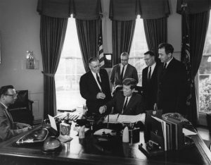 State representative Henry Reuss (second from the right) stands behind President John F. Kennedy as he signs a bill to limit wetland drainage in 1962.