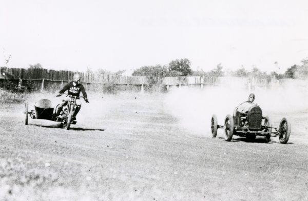 A man wearing a Harley Davidson jacket races an automobile driver at a track in Cedarburg some time in the 1920s.