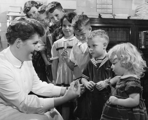 Seven siblings stand in line while waiting to receive their polio vaccination from a nurse in 1955.