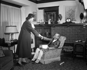 A visiting nurse greets her patient in his Milwaukee home in 1949.