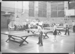 Four pairs of competitors take part in a table tennis tournament held in a Milwaukee gymnasium.
