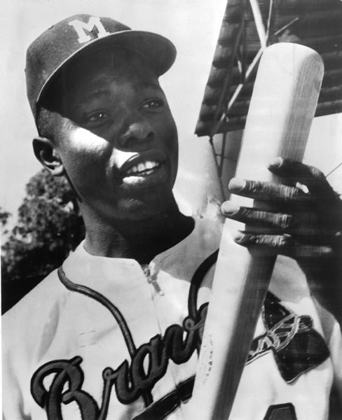 Hank Aaron holds a baseball bat while wearing his Milwaukee Braves uniform in this portrait.