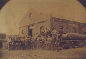 Illinois Steel employees stand in front of the rolling mill in Bay View in 1886. That same year, the mill was the site of strike spurred by the Eight-Hour Movement.