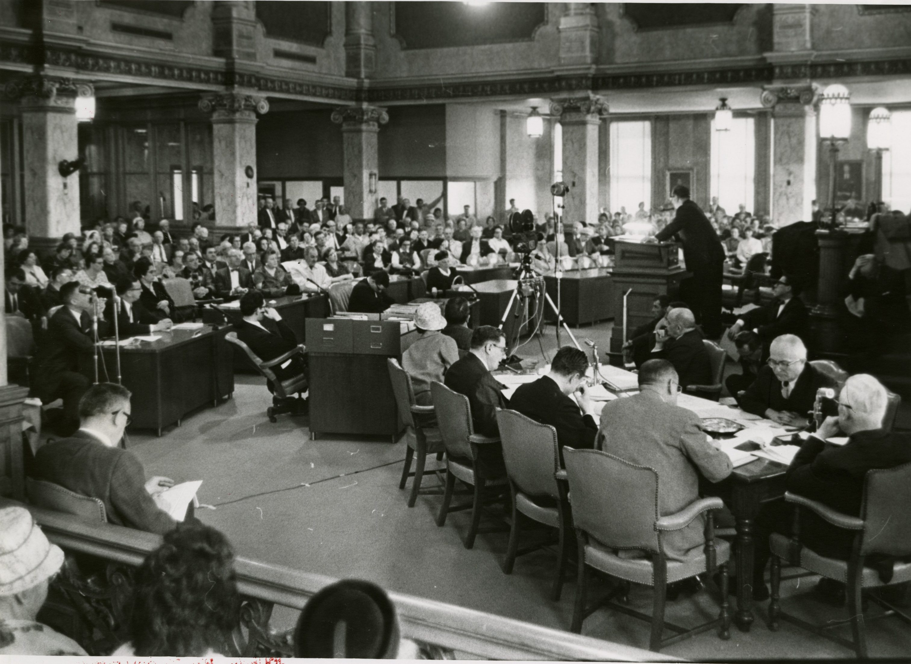 A man speaks at a podium to a crowd gathered for a hearing in regards to the Midtown public housing plant in the Milwaukee Common Council chambers in 1967.