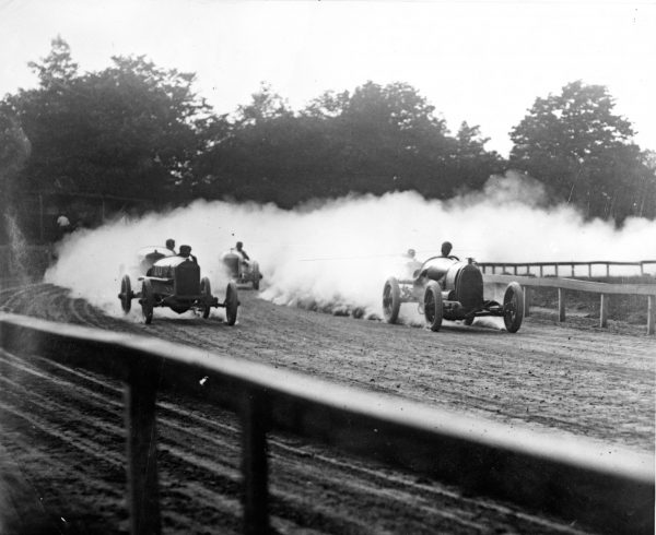 Several drivers race around the corner of a dirt track in 1923, leaving a cloud of dust in their wake.
