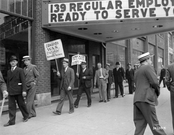 A group of workers from the Edwards Motor Company picket with strike signs on Wisconsin Avenue in 1937.