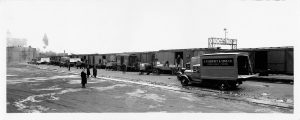 With the Chicago and North Western rail depot in the background, men from a variety of local companies, including the predecessor to Roundy's, load their products onto a train in 1934.